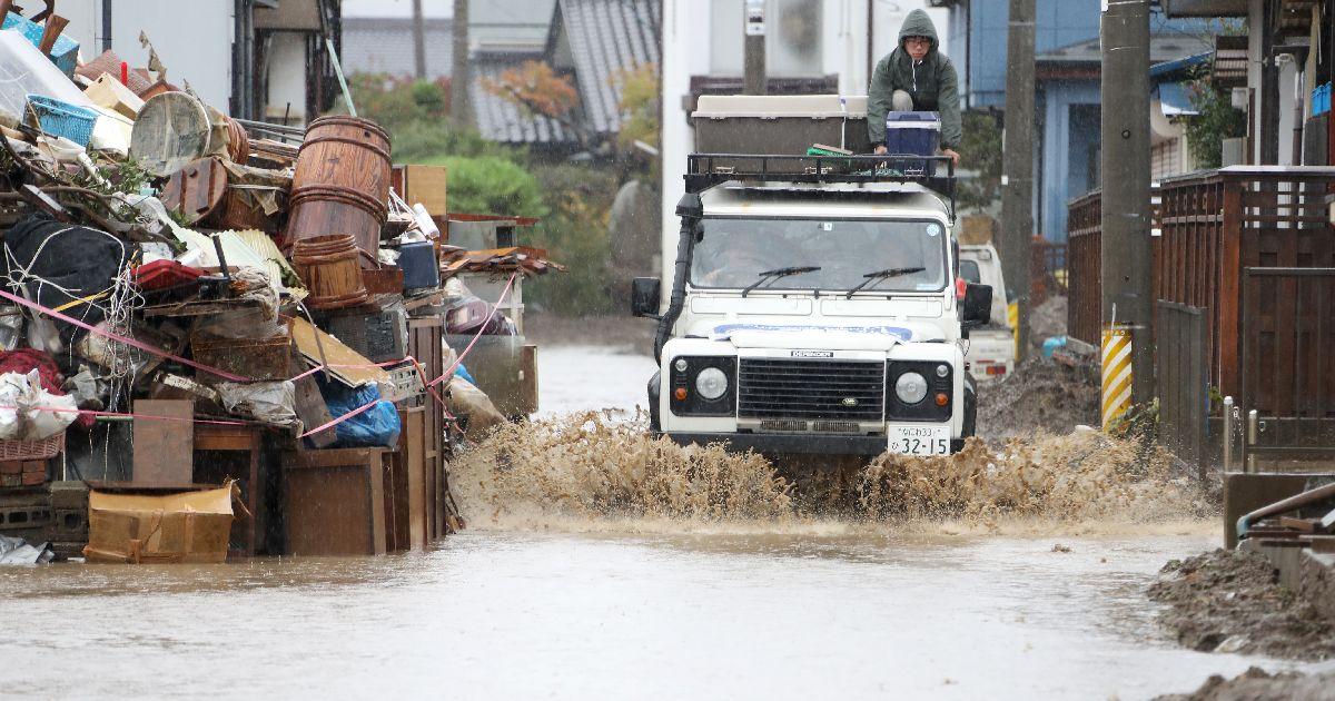 写真・図版 : 雨で冠水した道路脇にうずたかく積まれた災害ごみ置き場の横を、車が水をかき分けるように通っていた=2019年10月22日、長野市