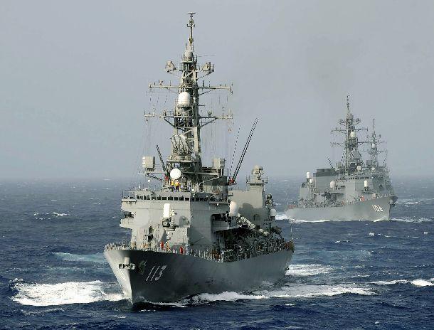写真・図版 : ソマリア沖での活動する海上自衛隊。補給艦「ときわ」から洋上補給を受けるため、「ときわ」の船尾方向から接近する、(手前から)護衛艦「さざなみ」と「さみだれ」 = 2009年6月6日、アデン湾洋上