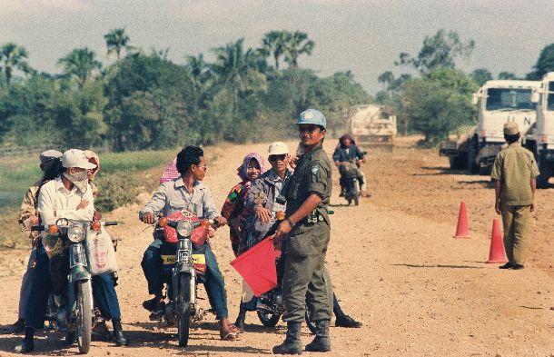 写真・図版 : UNTACに派遣。カンボジアタケオ州の国道の補修をする自衛隊。自衛隊員が旗を持ち交通整理もしている=1992年12月12日
