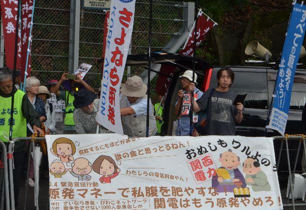 写真・図版 : 高浜原発のゲート前で横断幕を掲げて抗議する人たち=2019年10月8日、福井県高浜町の関西電力高浜原発