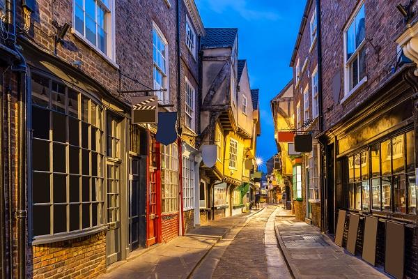 写真・図版 : 1350年ごろからの街並みが残る英国ヨーク中心部のシャンブルズ通り。古くは精肉業者が集まっており、肉が傷まないように日陰を増やすような建て方が残っている=shutterstock.com