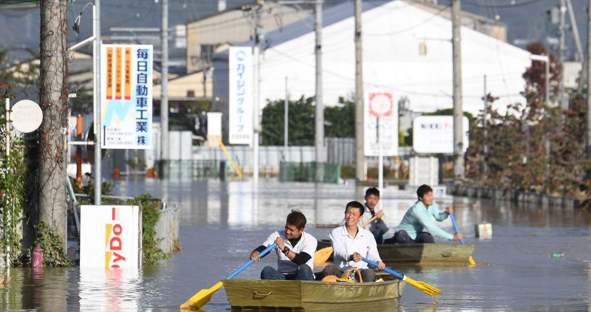 写真・図版 : 千曲川の氾濫で水没した穂保地区から救助などを終えて戻ってくる地域のボランティアの人たち=2019年10月13日、長野市