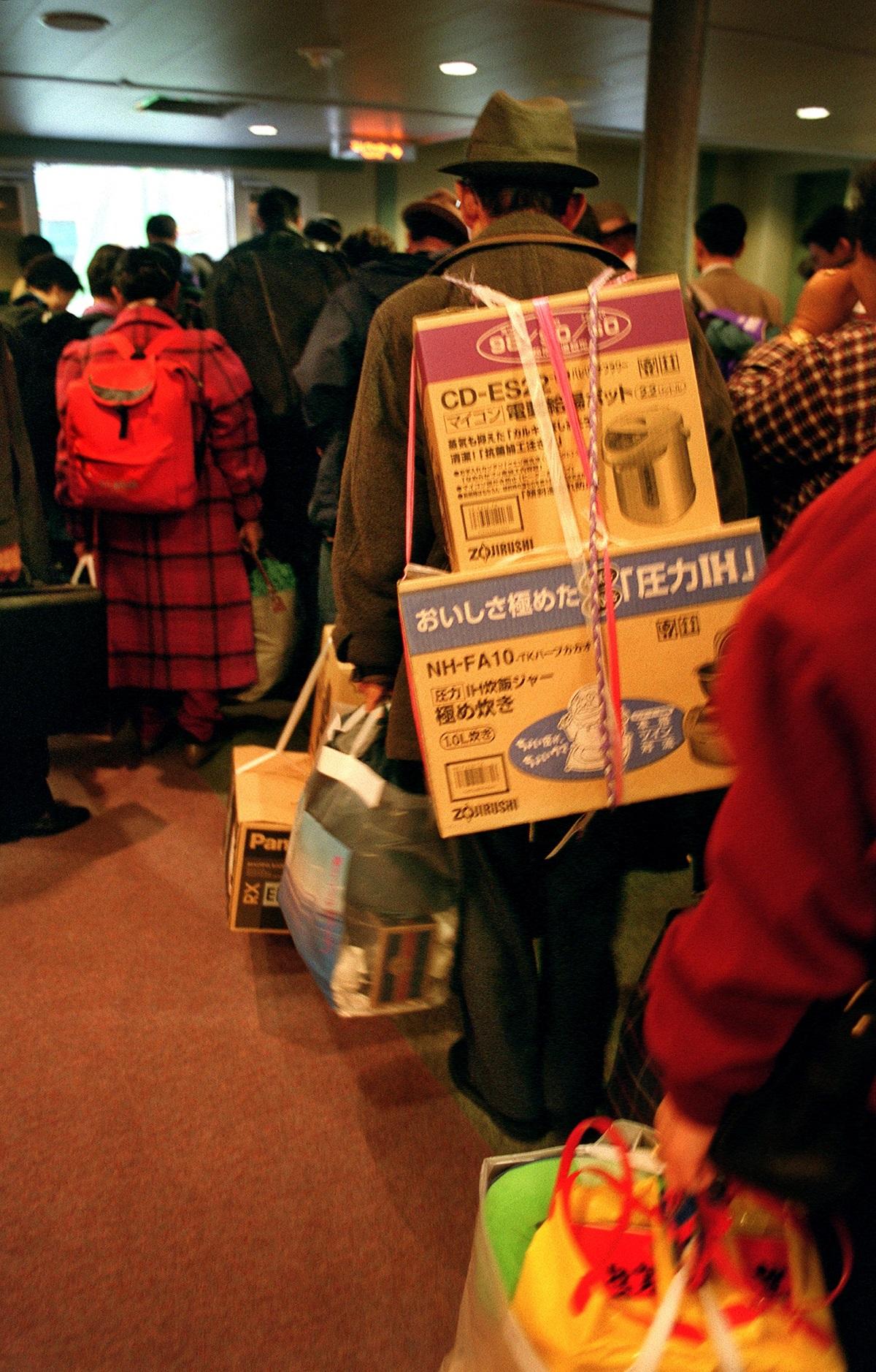 写真・図版 : 関釜フェリー「はまゆう」の船内で日本の電気製品を背負う男性=1999年