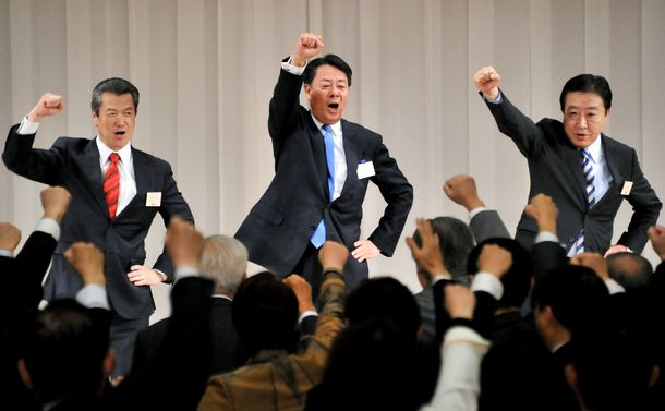 写真・図版 : 民主党新代表に就任した海江田万里氏(中央)は野田佳彦首相(右)、馬淵澄夫元国交相(左)と気勢を上げた=2012年12月25日、東京都港区