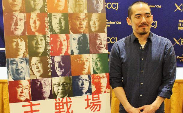 写真・図版 : 映画「主戦場」ポスターの横に立つミキ・デザキ監督=2019年4月4日、東京・丸の内の外国特派員協会