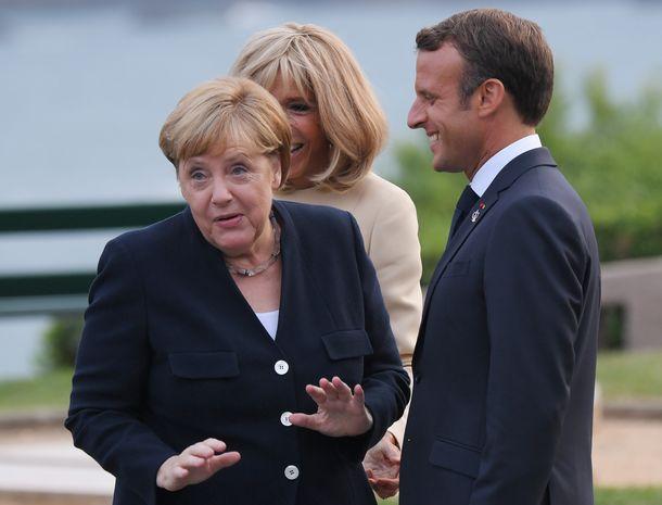 写真・図版 : マクロン仏大統領夫妻の出迎えを受けるメルケル独首相(左)=2019年8月24日、フランス・ビアリッツ