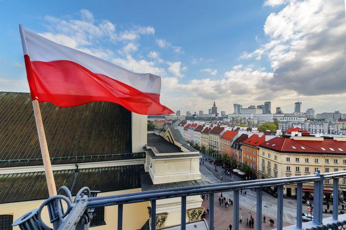 写真・図版 : ポーランド国旗とワルシャワ中心部(  Velishchuk Yevhen/Shutterstock.com)