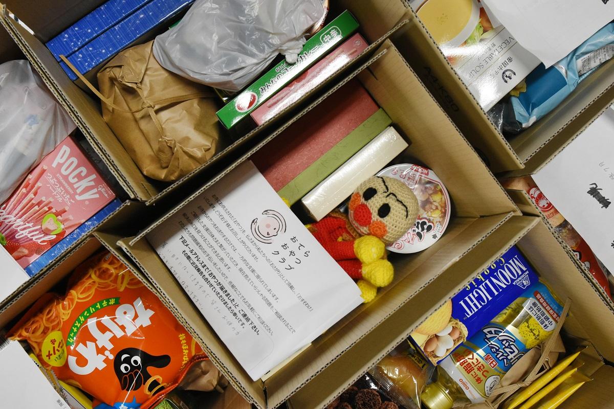 写真・図版 : 奈良県のおてらおやつクラブが困窮家庭向けに箱詰めした食品や手作りの人形