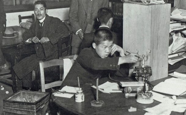 写真・図版 : 大阪朝日新聞の編輯(へんしゅう)局内で働く「子供さん」=明治の末ごろ