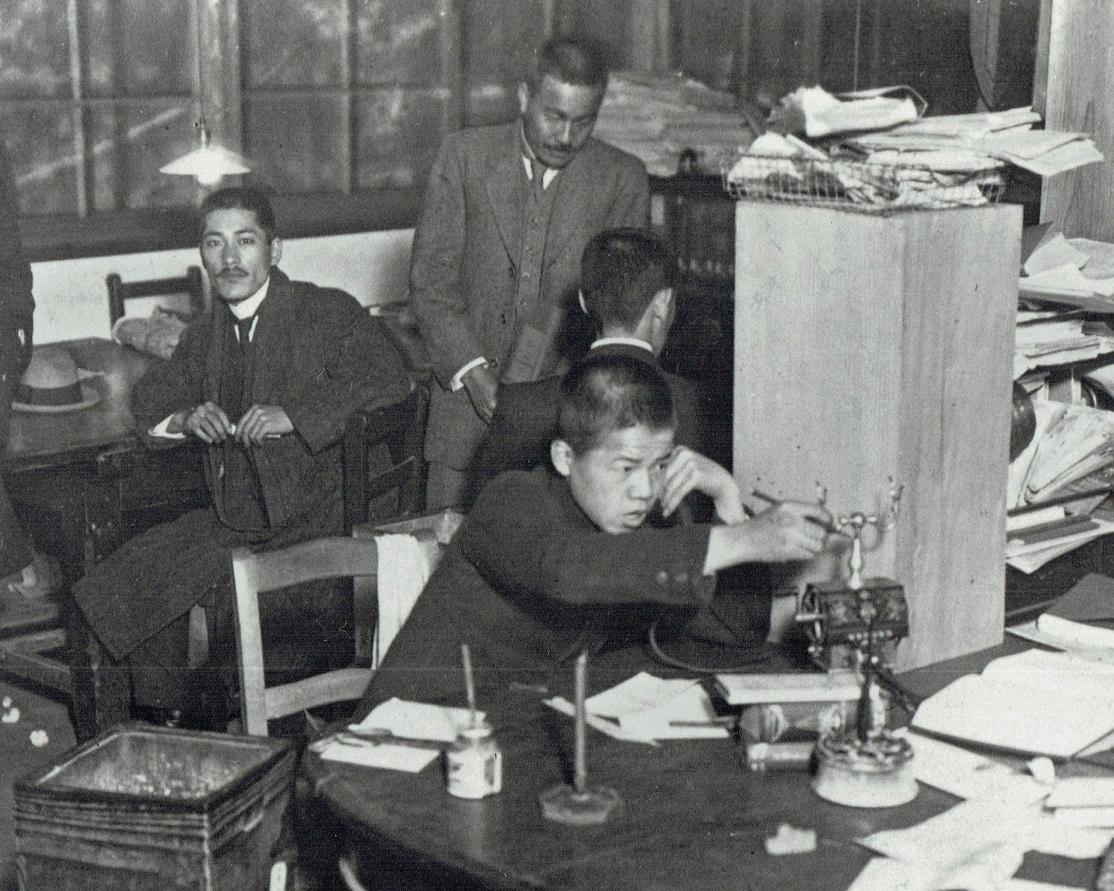 写真・図版 : 大阪朝日新聞の編輯局内で働く「子供さん」=明治の末ごろ
