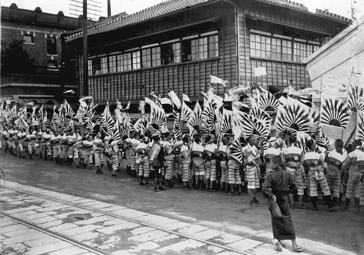 写真・図版 : 1915年(大正4)10月10日に夕刊発行の祝賀宣伝で、販売関係者たちが社章をあしらった旗で行列をした。後ろは大阪朝日新聞新築中の仮社屋