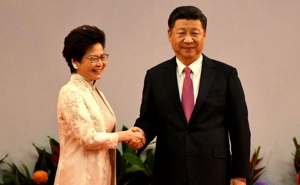 写真・図版 : 香港返還20年を記念する式典で握手をする中国の習近平国家主席(右)と香港の林鄭月娥行政長官=2017年7月1日、香港