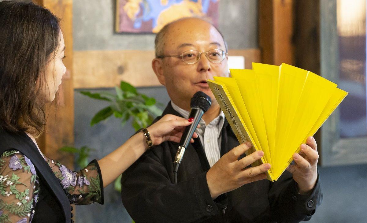 写真・図版 : 折本を広げる入口敦志・国文学研究資料館教授。左は筆者=2019年10月5日、京都市で開かれたワークショップ