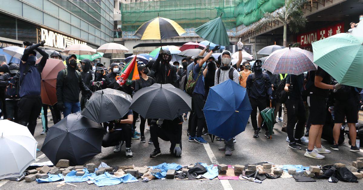 写真・図版 : 香港のデモは収まらない。警察の催涙弾に備えて雨傘を広げるデモ隊=2019年11月12日、香港・中環(セントラル