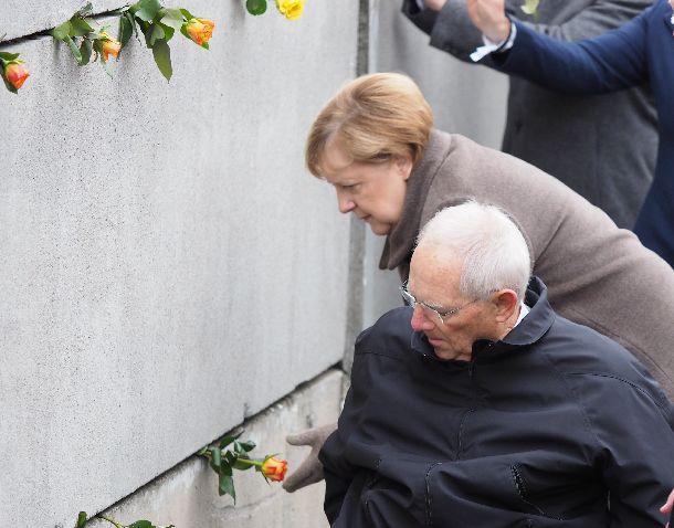 写真・図版 : ベルリンの壁崩壊から30周年の式典で、壁の隙間にバラの花を挿すドイツのメルケル首相(奥)=2019年11月9日、ベルリン