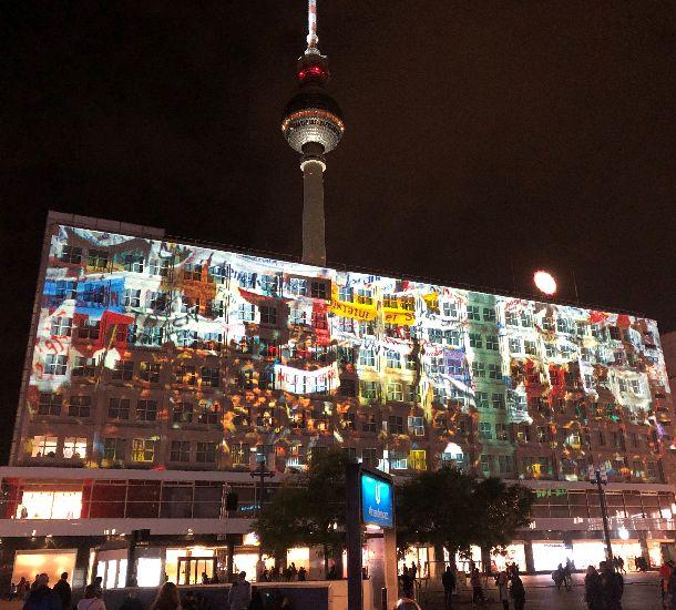 写真・図版 : ベルリンの壁崩壊から30年を記念し、市中心部の広場にあるビルの壁に当時の民主化運動などの映像が効果音とともに映し出された=2019年11月4日、ベルリン
