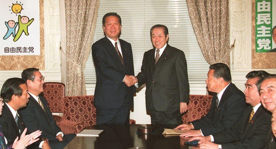 写真・図版 : 自民、自由両党の連立協議が合意し、連立政権へ向けた会談を前に握手する野中広務官房長官(右)と小沢一郎自由党党首=1999年1月13日、国会内で