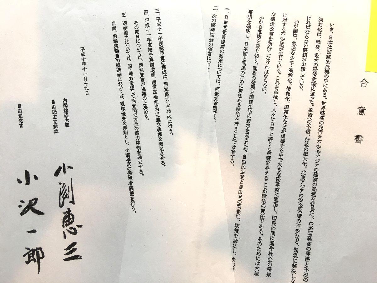 写真・図版 : 「小渕恵三」「小沢一郎」の署名のある「合意書」は全部で5項目。第1項目には「自由党党首提案の政策については、両党党首間で基本的方向で一致した。これに基づき直ちに両党間で協議を開始する。」とある。しかし、自民党側に実行の意思が見えず2000年4月1日、小沢は小渕に連立解消を申し入れた。奇しくもその夜、小渕は帰らぬ人となった。