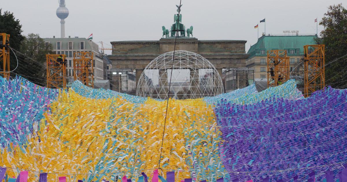 写真・図版 : 30年前の民主化運動に対するメッセージが書かれた短冊で飾られたブランデンブルク門=2019年11月1日、ベルリン。野島淳撮影