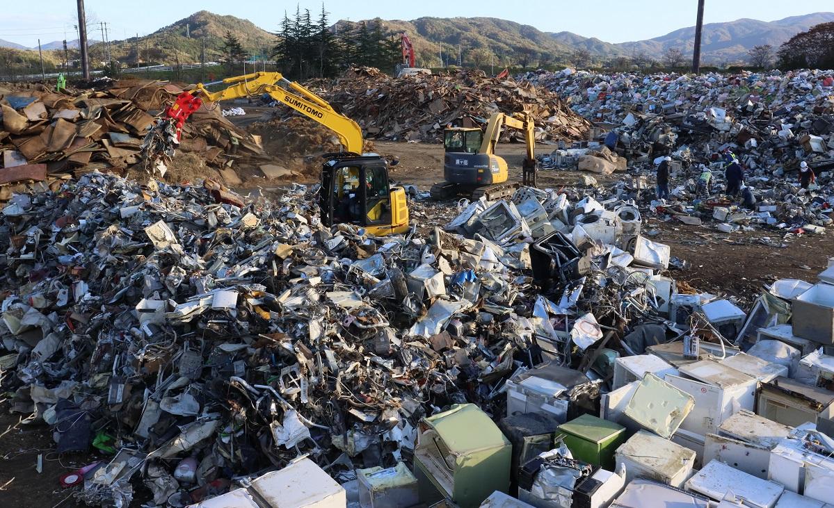 写真・図版 : 町民グラウンドに山積みになった「災害ゴミ」=宮城県丸森町