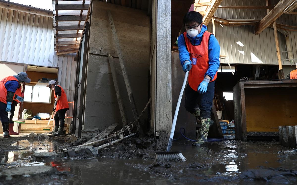 写真・図版 : 台風被害を受けた住宅兼作業所で、泥をかき出す仙台市から来たボランティア=宮城県丸森町