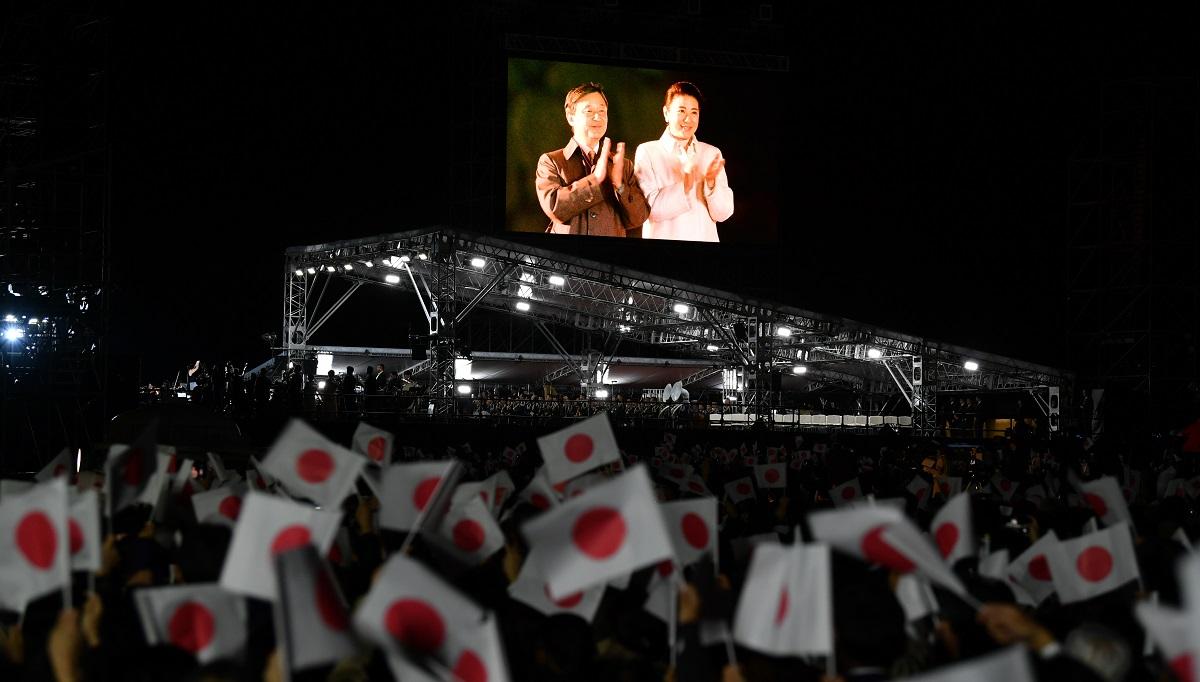 写真・図版 : 嵐が歌う奉祝曲に拍手をする両陛下が映し出された「国民祭典」の会場