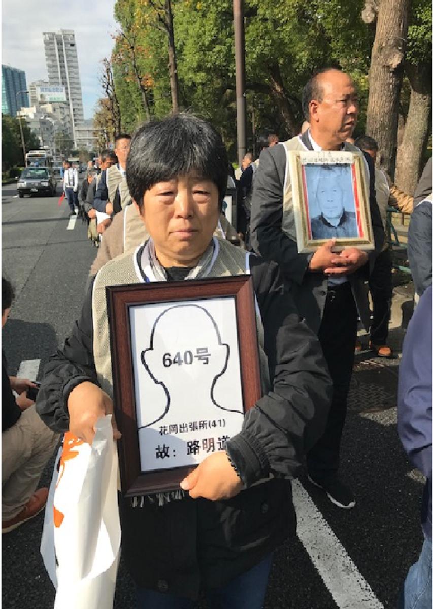写真・図版 : 名前と輪郭、番号が書かれた祖父の「遺影」を抱えて歩く路桂英さん=2019年11月19日、東京都内、筆者撮影