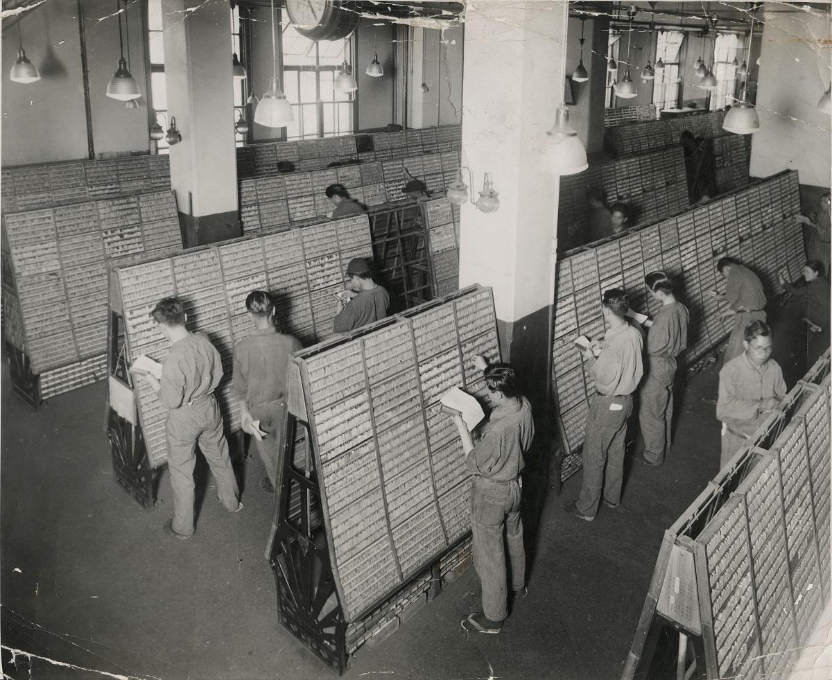 写真・図版 : 1934年当時の活字ケース群と活字を拾う文選の風景。大阪朝日新聞社で