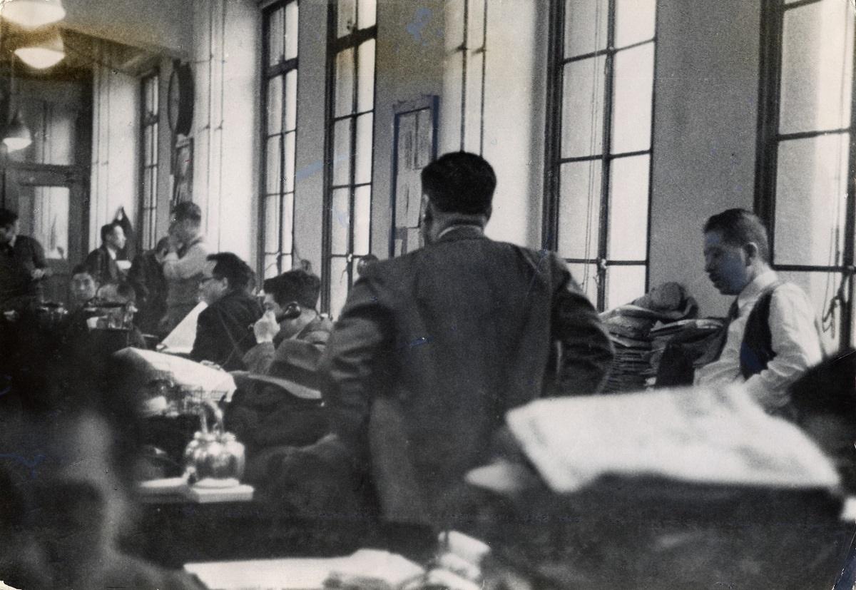 写真・図版 : 二・二六事件で襲撃された直後の東京朝日新聞社編輯局。ただしこの写真が1966年の社内報に掲載された時には「二十六日の午後の一情景」という説明が付いている。手前の背中が主筆の緒方竹虎、その右が編輯局長の美土路昌一
