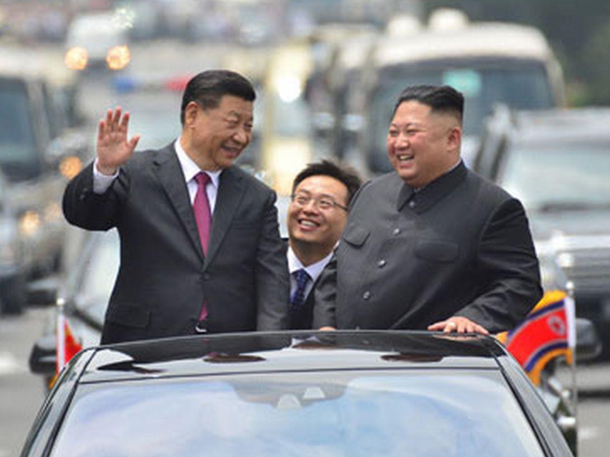 写真・図版 : 6月、訪朝した中国の習国家主席とオープンカーに乗る北朝鮮の金委員長=平壌。労働新聞ホームページから