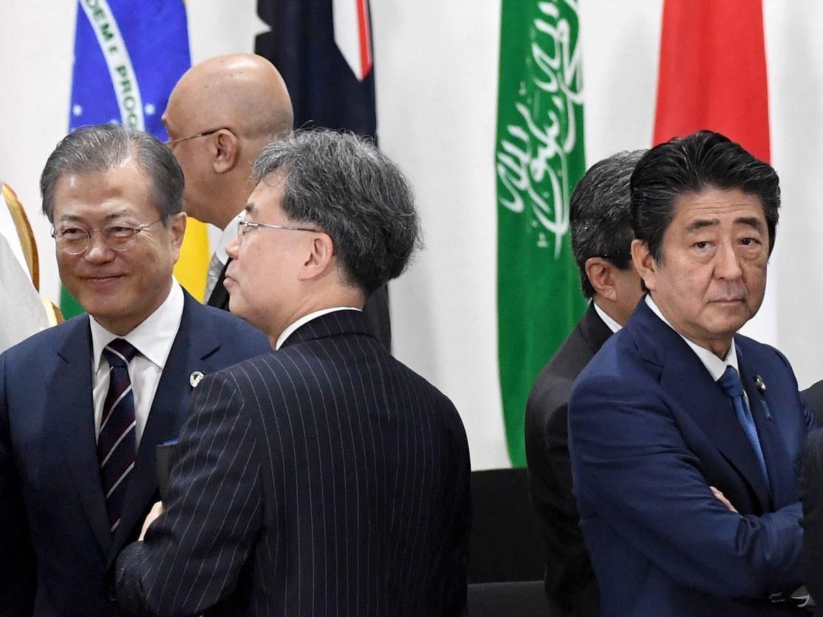 写真・図版 : 6月、大阪でのG20首脳会議で握手を交わした後、開始を待つ安倍首相(右)と文大統領(左端)=大阪市。代表撮影