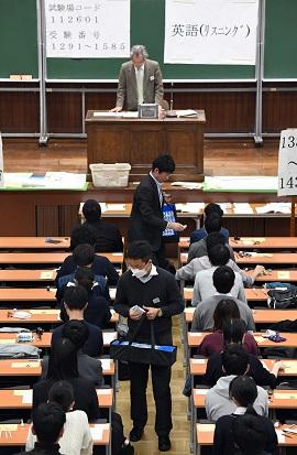 写真・図版 : 大学入試センター試験で、受験生にリスニング用の機器を配布する担当者=2019年1月19日、東京都文京区の東京大学、代表撮影