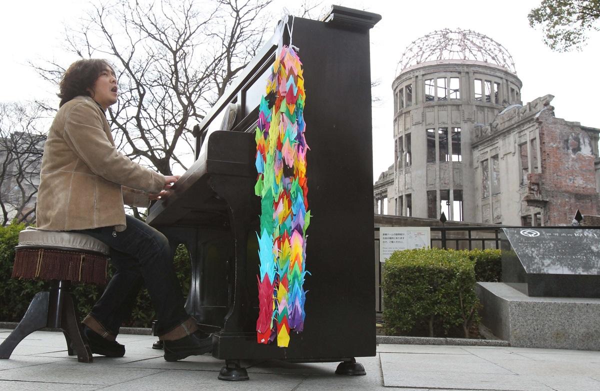 写真・図版 : 原爆ドーム前で被爆ピアノを演奏する原田真二=2010年