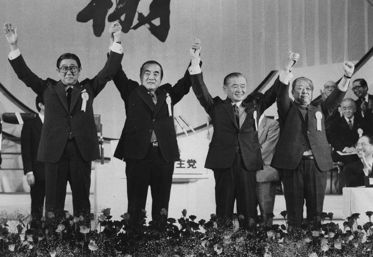 写真・図版 : 自民党総裁選で中曽根康弘首相(総裁)から後継総裁に指名された竹下登幹事長が第12代総裁(任期2年)に正式に就任。壇上で手をつなぎ、団結を誇示する左から安倍晋太郎総務会長、中曽根首相、竹下総裁、宮沢喜一蔵相= 1987年10月31日  、 東京・千代田区の日比谷公会堂