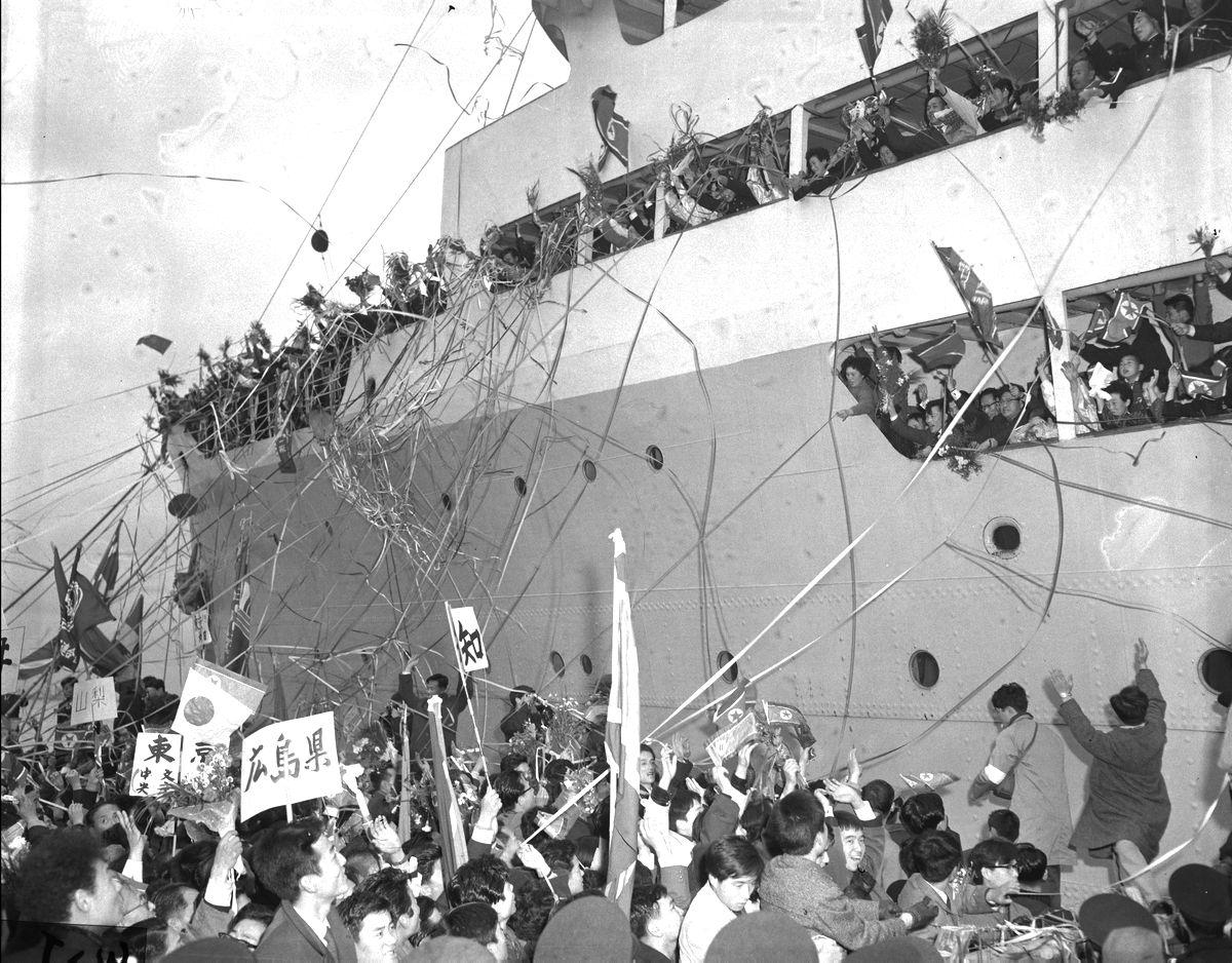 写真・図版 : 1959年12月14日、新潟港から北朝鮮・清津港へ向かう帰国船クリリオン号。甲板上の帰国者と見送りの人々、「マンセー(万歳)」のかけ声でごった返した