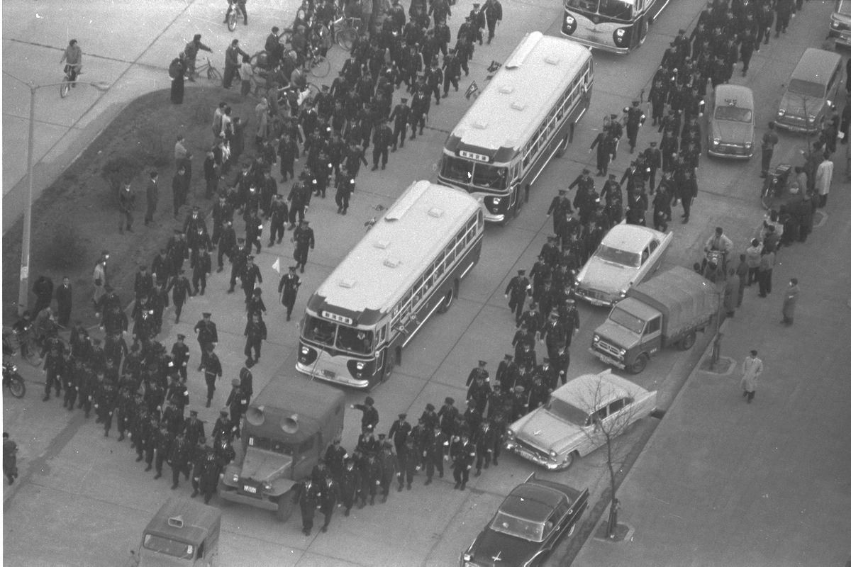 写真・図版 : 北朝鮮への帰国第一陣を乗せて新潟入りしたバス。新潟駅前では妨害を防ぐため、警官1300人が動員された=1959年12月11日