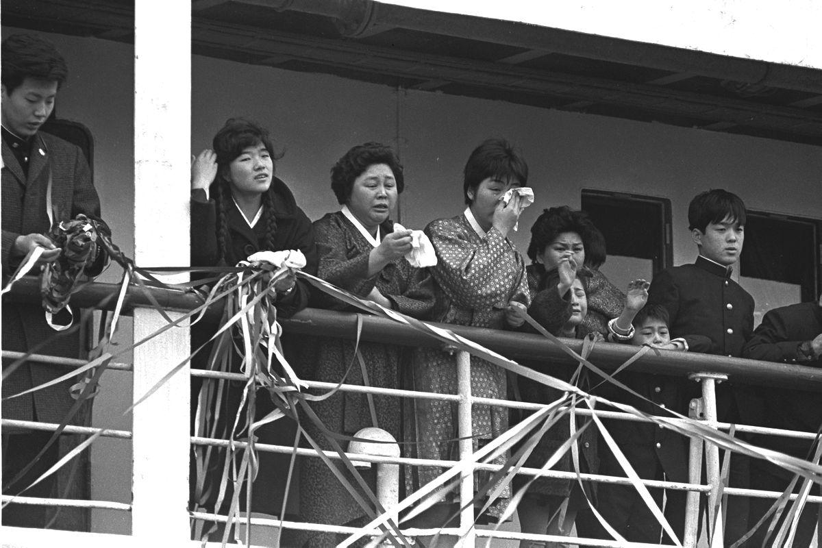 写真・図版 : 新潟港を出発する帰還船のデッキで手を振るチマ・チョゴリ姿の帰還者たち=1964年3月