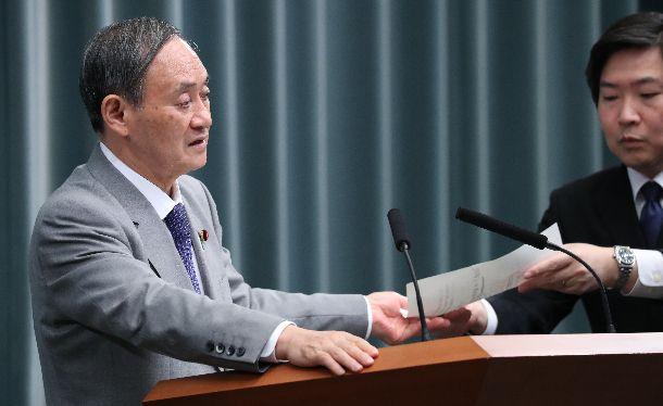写真・図版 : 記者会見でメモを受け取りながら質問に答える菅義偉官房長官=2019年12月4日、首相官邸