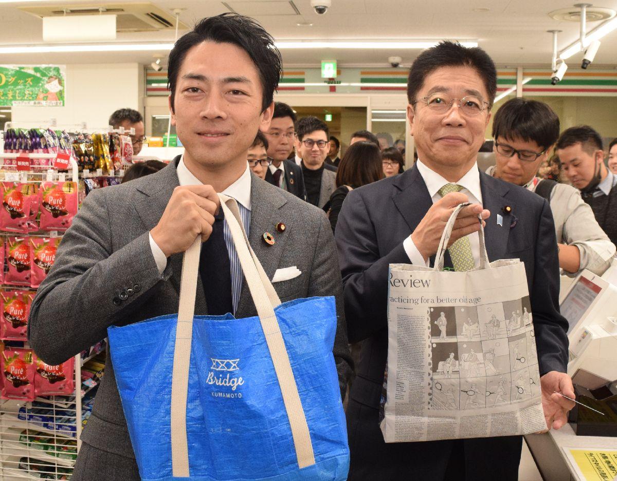 写真・図版 : 庁舎内のコンビニでマイバッグを使って買い物をした小泉進次郎環境相(左)と加藤勝信厚生労働相=東京・霞ケ関