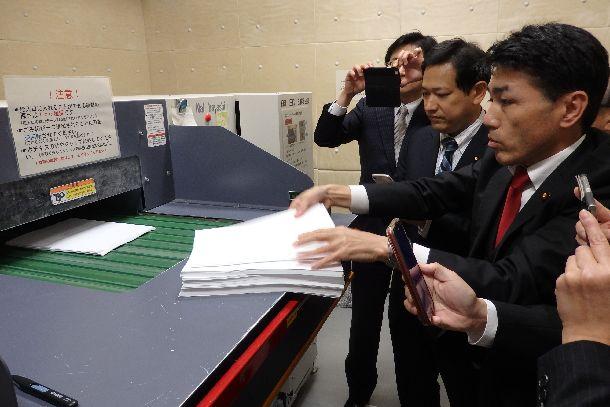 写真・図版 : 桜を見る会の招待者の名簿が廃棄された大型シュレッダーで、実際に800枚の紙を細断した野党の追及本部のメンバー=2019年11月26日、内閣府