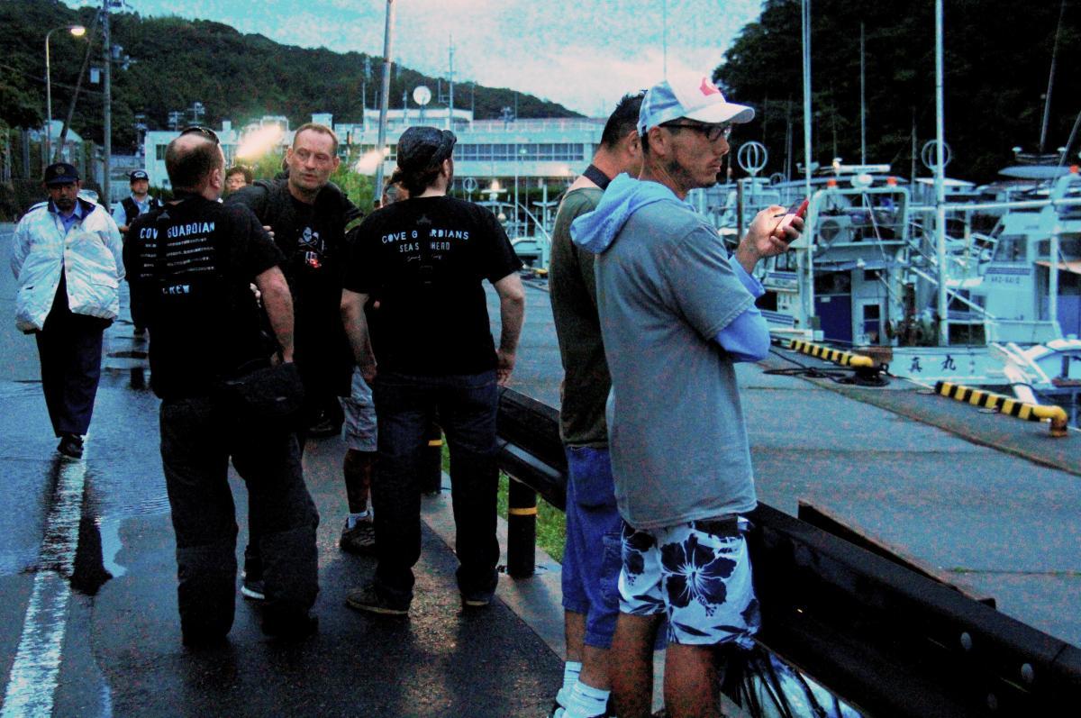 写真・図版 : 警察官が警戒するなか、イルカ漁に反対する団体のメンバーが港に集まった=2014年9月、和歌山県太地町