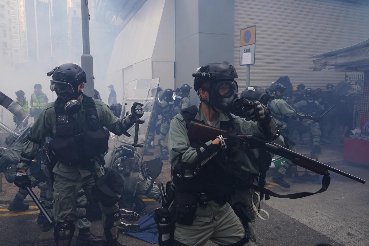 写真・図版 : 銃を構えてデモ隊を制圧する警官=2019年10月1日