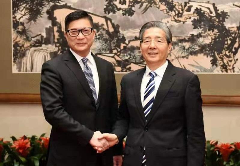 写真・図版 : 握手する香港警察の鄧炳強・警務処長(左)と中国共産党中央政法委員会の郭声琨・書記=2019年12月7日、北京