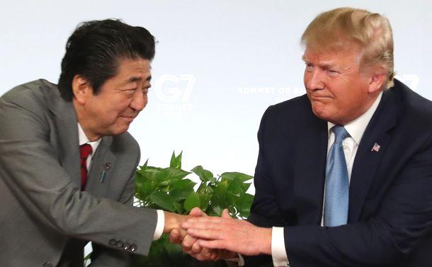 写真・図版 : トランプ米大統領(右)との首脳会談に臨み、握手を交わす安倍晋三首相=2019年8月25日、フランス・ビアリッツ