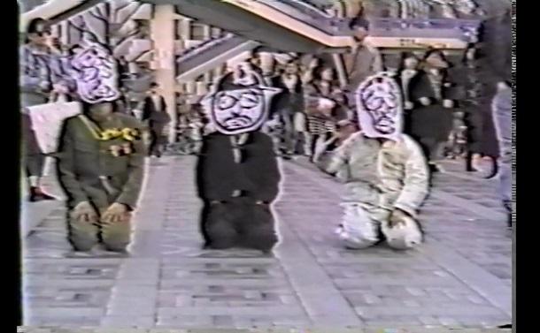 写真・図版 : 原宿駅前の神宮橋に座る3人の「昭和天皇」。戦前から戦後への天皇制の連続性を示そうとしたパフォーマンスだという(以下カラー写真は映画『秋の嵐 Harajuku im herbst』から)=1988年12月4日
