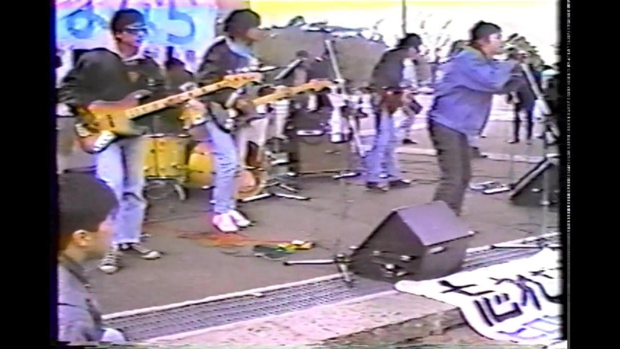 写真・図版 : 前週1月8日の逮捕に対する抗議ライブ。この直後、演奏を控えていたバンドのメンバーらが逮捕される。後ろに見える横断幕を勝手に貼り付けたという「軽犯罪法違反」だった=1989年1月15日、東京・代々木公園