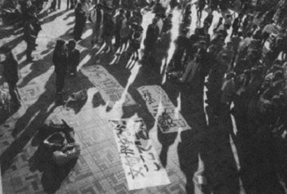 写真・図版 : 大勢の通行人が足を止め耳を傾けている。「文句があるならここで言え!」という新しい横断幕=90年11月12日