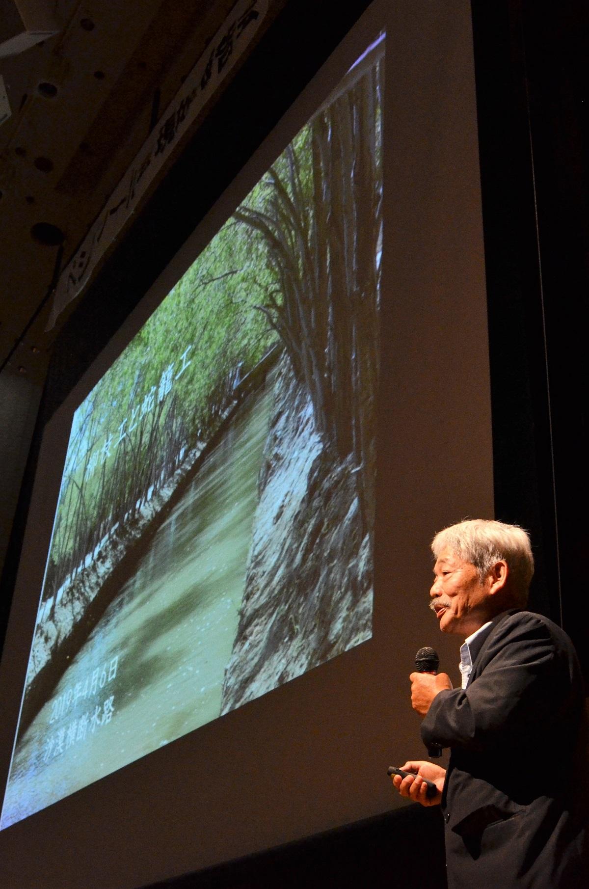 写真・図版 : 緑が茂る用水路の写真を示し、アフガンでの活動を語る中村哲さん=2019年6月1日、福岡市の西南学院大学