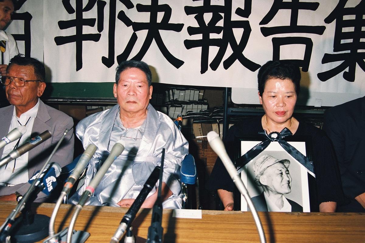 写真・図版 : 1994年7月、戦傷年金不支給の取り消しを求めた裁判で請求が棄却された後、記者会見を開く原告・石成基さん(中央左)。もう一人の原告・陳石一さんは判決の2カ月前に亡くなり、妻の堺正子さんが遺影を抱えて臨んだ=東京・霞が関
