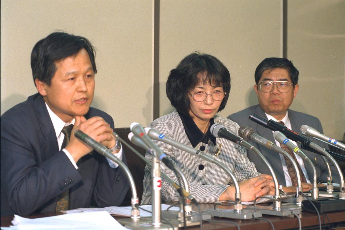 写真・図版 : 外国人の公務員採用・任用条件をめぐる初の司法判断となった東京都の管理職試験をめぐる裁判。東京地裁に訴えを退けられ記者会見する在日韓国人2世、鄭香均さん(中央)の隣には金敬得弁護士が座った=1996年5月16日、東京地裁